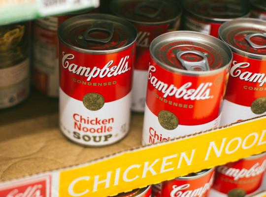 tins of chicken noodle soup on supermarket shelf