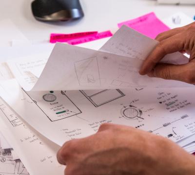 hands flipping through design sketches