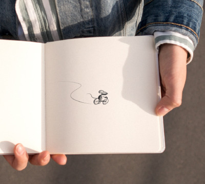 person holding sketch book with drawing of mouse on tricycle